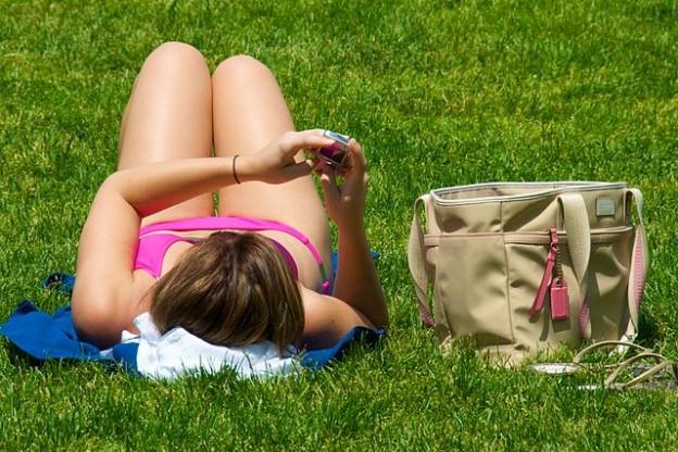 640px-Texting_while_sunbathing
